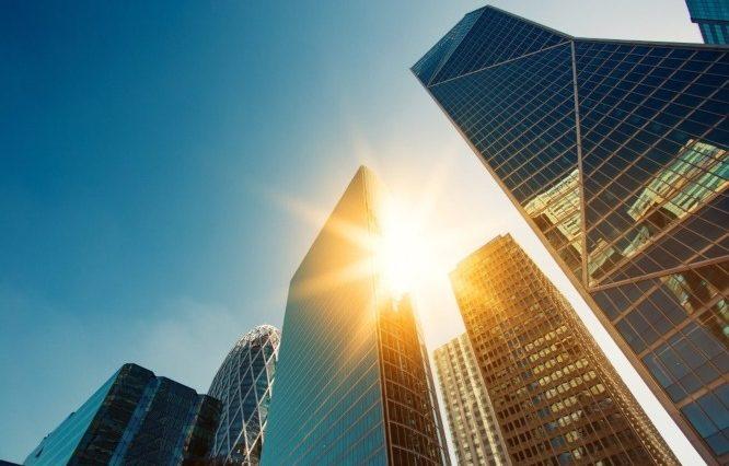 sun beams passing city skyscrapers