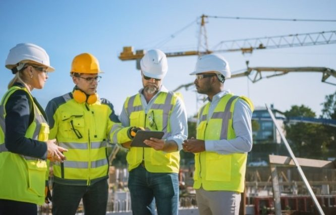 four construction workers looking at one ipad and discussing
