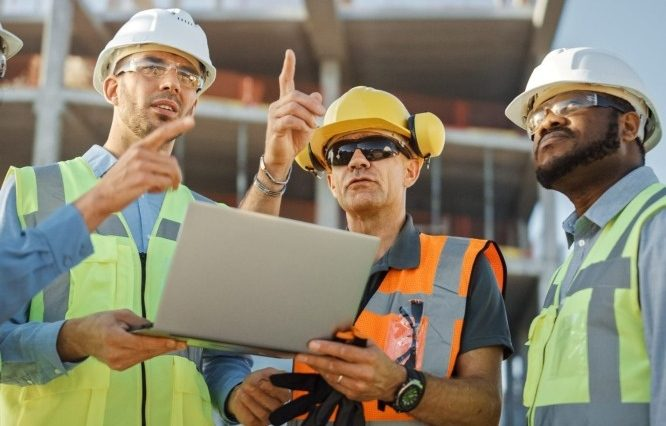 three construction workers observing a construction site whilst looking at a laptop