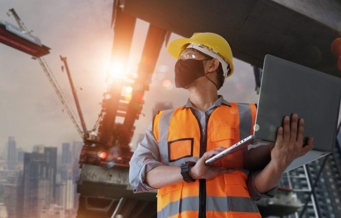 a construction worker wearing a face covering and using his work laptop